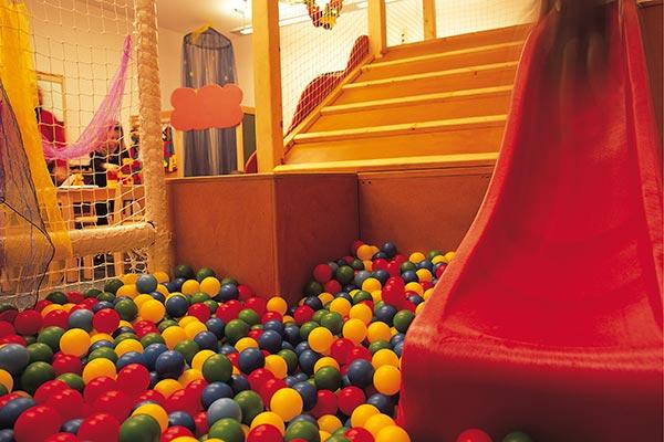stanza giochi bambini con palline colorate, scivolo e reti