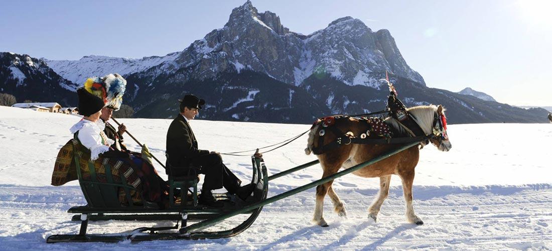slitta con 2 passeggeri sulla neve trainata da cavallo